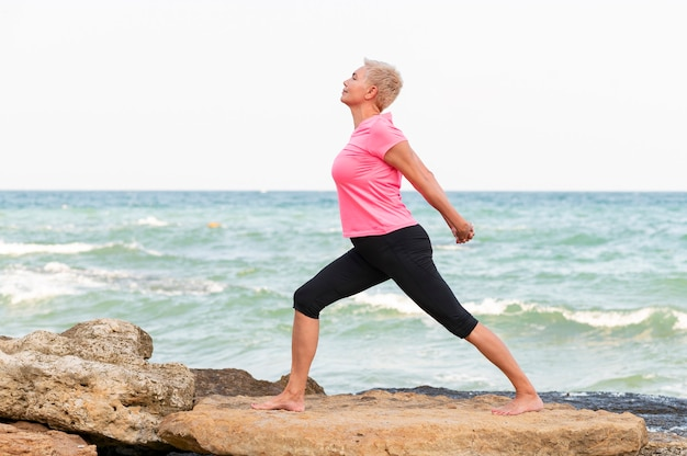 Счастливая женщина средних лет на берегу моря делает упражнения на растяжку. портрет вид сбоку