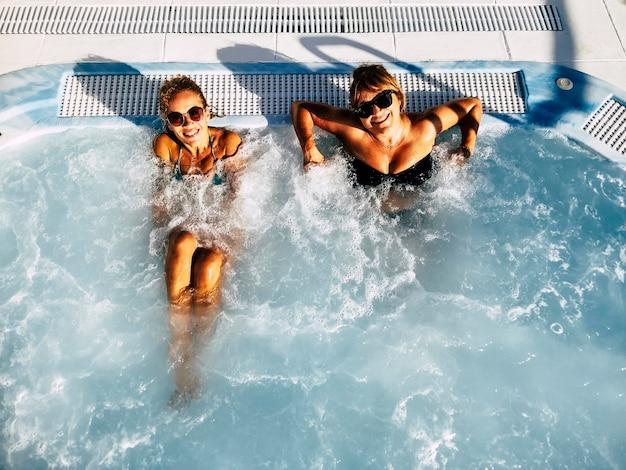 幸せな中年の女性のカップルは、リゾートホリデーホテルの休暇で一緒に泡プールを楽しんでいます