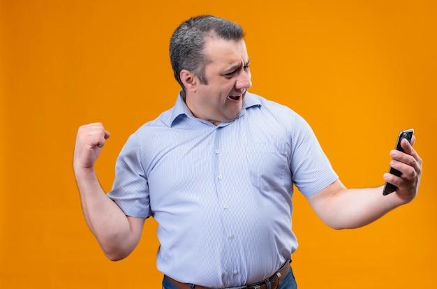 Счастливый мужчина средних лет в синей полосатой рубашке смотрит в свой мобильный телефон и поднимает руку в жесте триумфа стоя