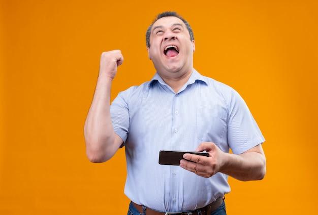 Felice uomo di mezza età che indossa la maglietta blu spogliata, vincendo il gioco sul cellulare e alzando la mano nel gesto di trionfo mentre si trova in piedi