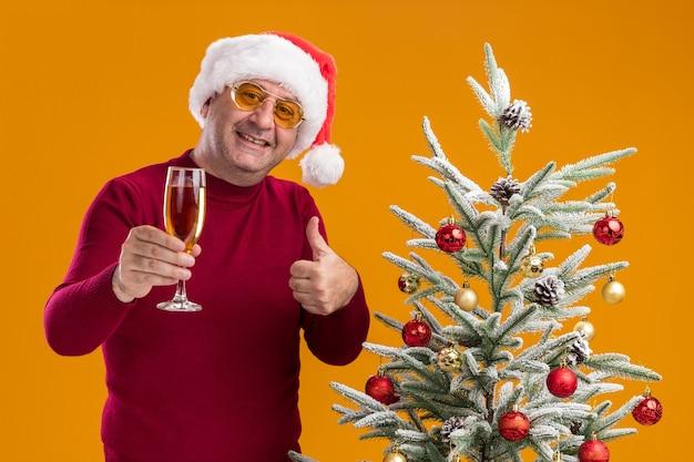 Felice uomo di mezza età che indossa il cappello di babbo natale in dolcevita rosso scuro e occhiali gialli con un bicchiere di champagne sorridente che mostra i pollici in su in piedi accanto a un albero di natale sul muro arancione