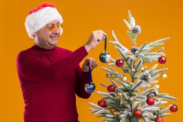 Счастливый мужчина среднего возраста в новогодней шапке санта-клауса в темно-красной водолазке и желтых очках улыбается, украшая елку, стоящую над оранжевой стеной