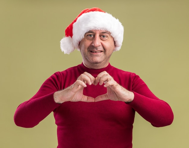 Happy middle age man wearing christmas santa hat making heart gesture smiling cheerfully  standing over green  background