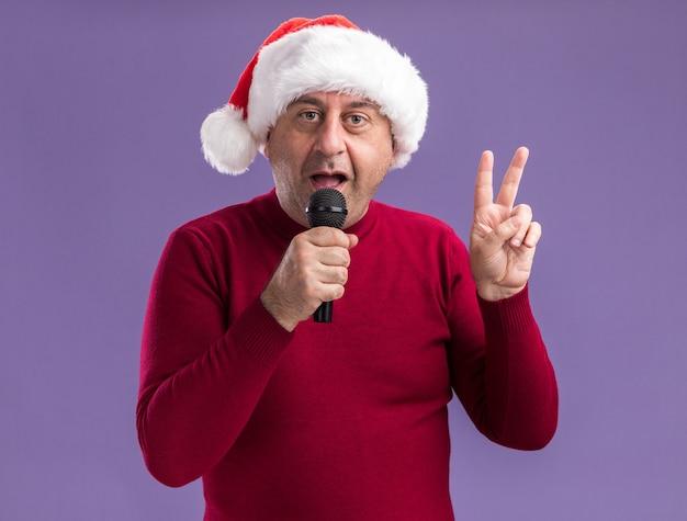 보라색 배경 위에 서있는 카메라를보고 v 기호를 보여주는 마이크에 얘기하는 크리스마스 산타 모자를 쓰고 행복한 중년 남자