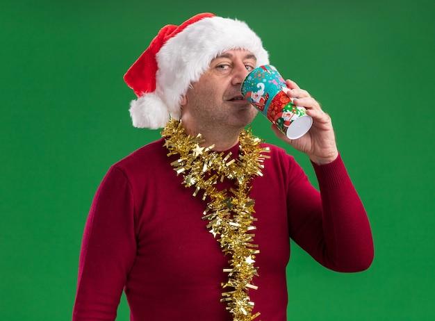 Felice uomo di mezza età che indossa il cappello di babbo natale con orpelli intorno al collo che beve dalla tazza di carta colorata in piedi su sfondo verde