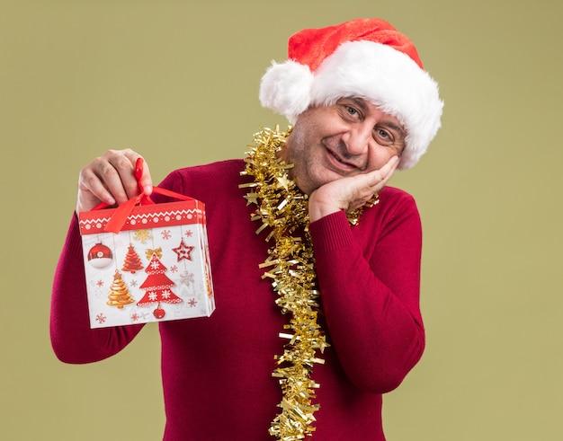Счастливый мужчина среднего возраста в рождественской шляпе санта-клауса с мишурой на шее держит рождественский подарок, глядя в камеру, весело улыбаясь, стоя на зеленом фоне