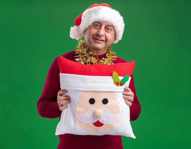 緑の背景の上に立っている顔に笑顔でカメラを見てクリスマス枕を保持している首の周りに見掛け倒しのクリスマスサンタ帽子をかぶって幸せな中年男性