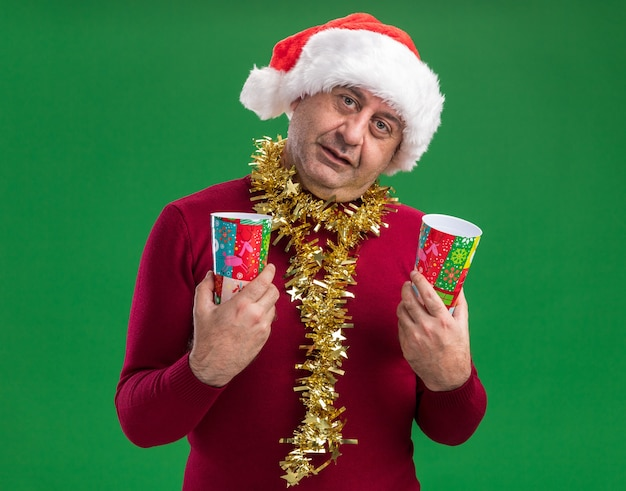 녹색 배경 위에 서 웃는 카메라를보고 다채로운 종이 컵을 들고 목에 반짝이와 크리스마스 산타 모자를 쓰고 행복 한 중년 남자