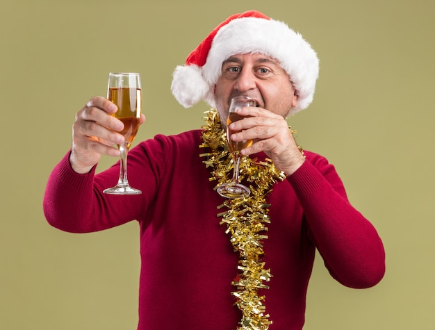 Happy middle age man wearing christmas santa hat with tinsel around neck holding glasses of champagne  drinking standing over green  wall