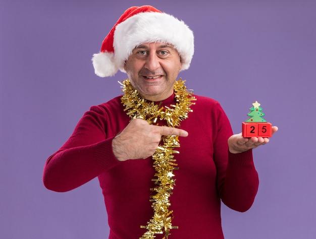 Счастливый мужчина среднего возраста в рождественской шляпе санта-клауса с мишурой на шее держит игрушечные кубики с датой двадцать пять, указывая указательным пальцем на них, улыбаясь, стоя на фиолетовом фоне
