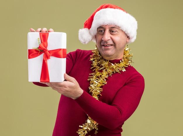 녹색 벽 위에 유쾌하게 서있는 크리스마스 선물을 보여주는 목 주위에 반짝이와 크리스마스 산타 모자를 쓰고 행복한 중년 남자