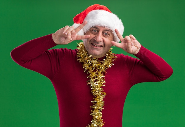 녹색 벽 위에 서있는 눈 근처 v 기호를 보여주는 미소 목 주위에 반짝이 크리스마스 산타 모자를 쓰고 행복 한 중년 남자