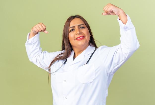 청진기를 들고 흰 코트를 입은 행복한 중년 여성 의사는 승자처럼 자신감 있게 주먹을 들고 웃고 있다