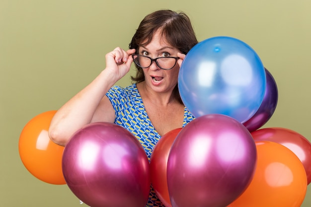 Happy middle age woman in glasses with bunch of colorful balloons  surprised