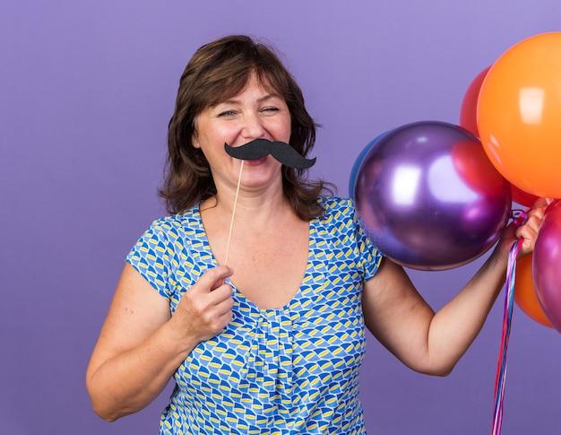 Felice donna di mezza età che tiene in mano un mazzo di palloncini colorati e baffi divertenti su un bastone divertendosi
