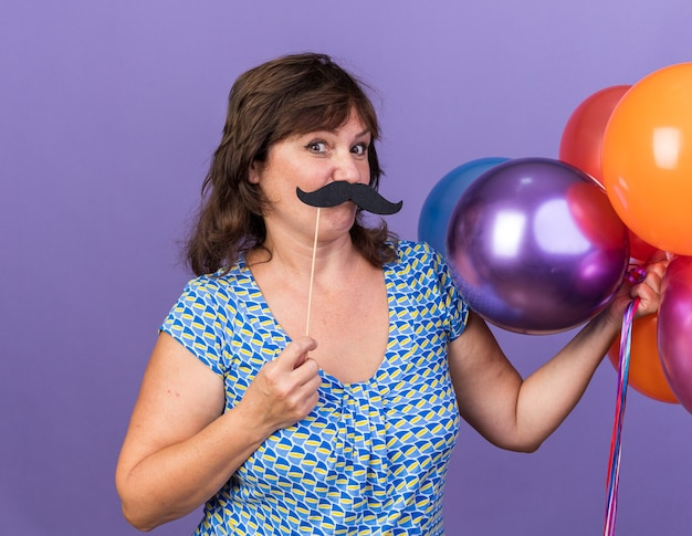 Happy middle age woman holding bunch of colorful balloons and funny mustache on stick having fun