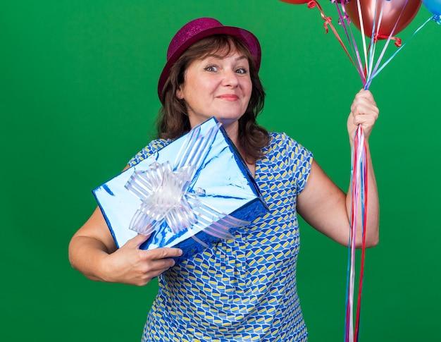 カラフルな風船を持ったパーティーハットをかぶった幸せな中年女性と、緑の壁の上に立って誕生日パーティーを陽気に祝う笑顔のプレゼント