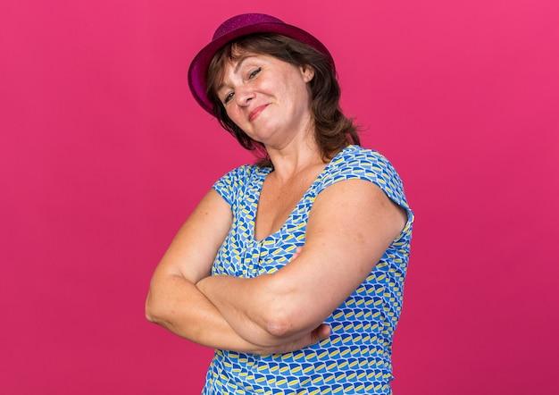 Счастливая женщина среднего возраста в партийной шляпе, уверенно улыбаясь