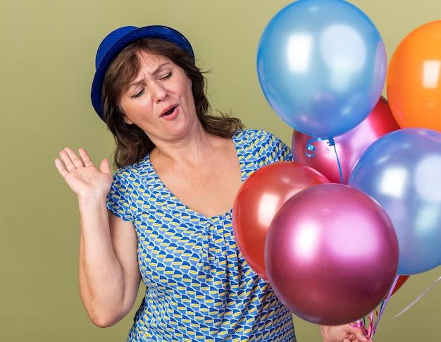 녹색 벽 위에 서있는 생일 파티를 축하하는 재미 다채로운 풍선의 무리와 함께 파티 모자에 행복 중년 여자