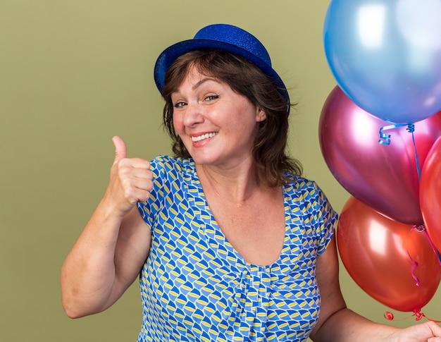 녹색 벽 위에 서있는 생일 파티를 축하 엄지 손가락을 보여주는 미소 다채로운 풍선의 무리와 함께 파티 모자에 행복 중년 여자
