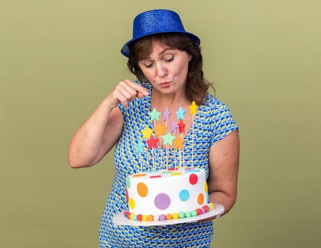 Felice donna di mezza età con cappello da festa che tiene in mano una torta di compleanno guardandola incuriosita