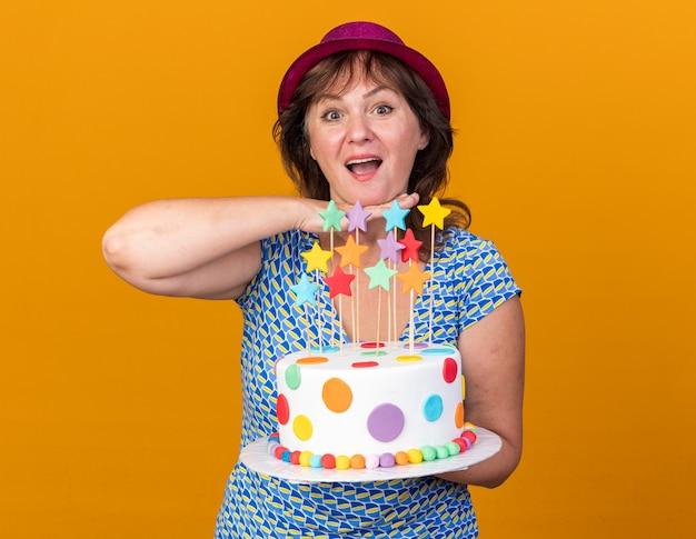 Felice donna di mezza età con cappello da festa che tiene in mano una torta di compleanno che sorride allegramente