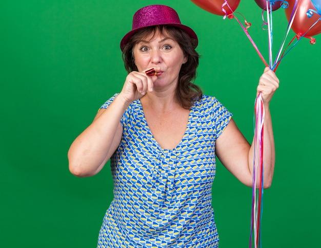 Felice donna di mezza età con cappello da festa che tiene palloncini colorati che soffiano fischietto felice e allegra che celebra la festa di compleanno in piedi sul muro verde green