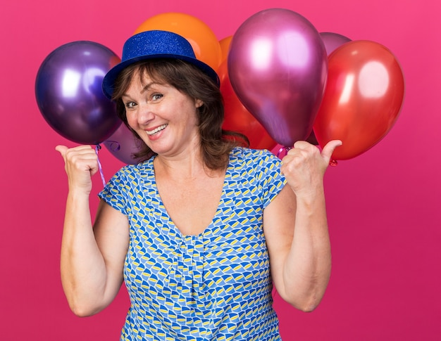 Felice donna di mezza età con cappello da festa che tiene palloncini colorati sorridenti allegramente mostrando i pollici in su