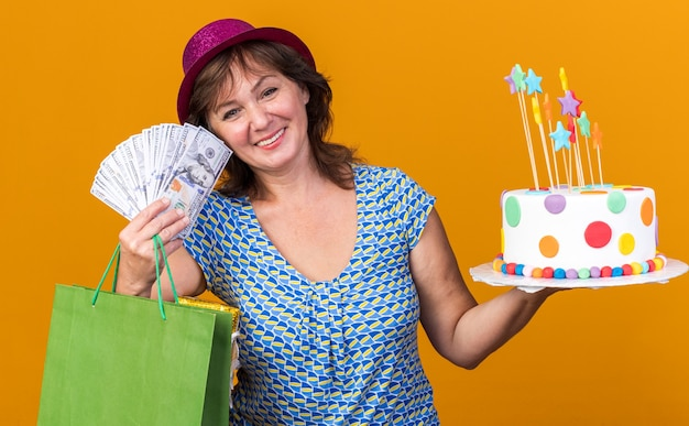 Happy middle age woman in party hat holding paper bag with gifts holding birthday cake and cash  smiling broadly