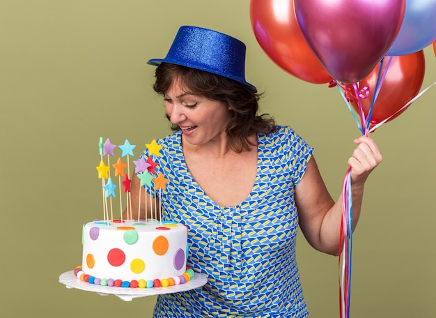 Happy middle age woman in party hat with bunch of colorful balloons holding birthday cake looking at it smiling celebrating birthday party standing over green wall