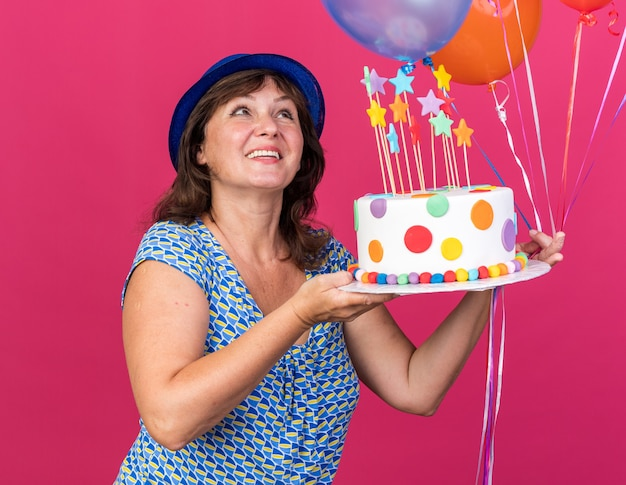 Happy middle age woman in party hat with colorful balloons holding birthday cake looking up with smile on face celebrating birthday party standing over pink wall