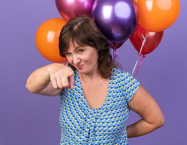 Felice donna di mezza età con un mucchio di palloncini colorati che puntano con il dito indice sorridendo allegramente festeggiando la festa di compleanno in piedi sul muro viola