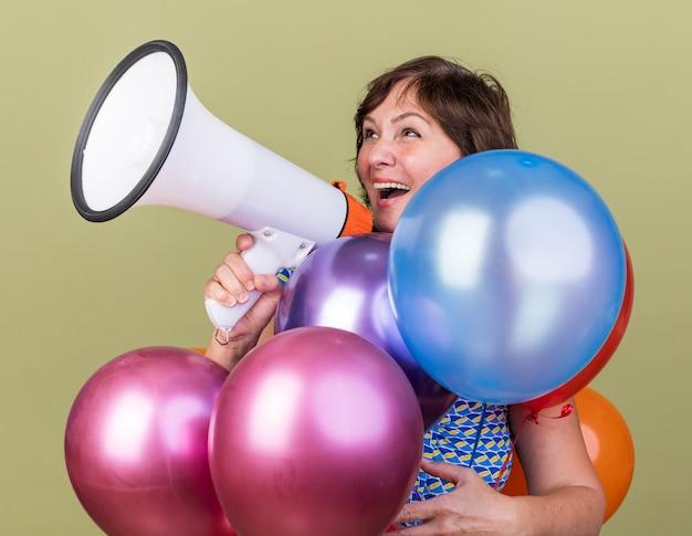 확성기로 외치는 다채로운 풍선의 무리와 함께 행복 한 중년 여자