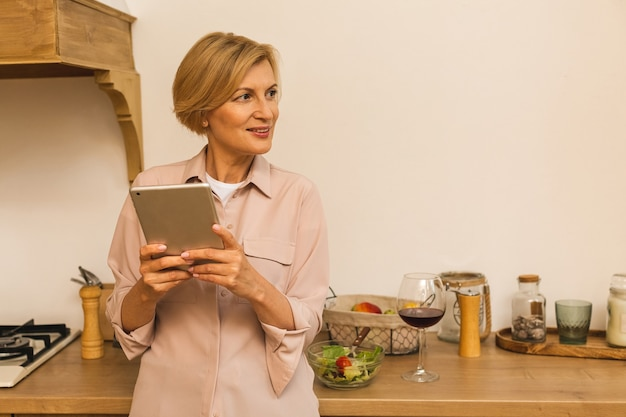 Happy middle aged 50 years old woman using digital tablet sitting in kitchen at home. mature older lady  holding pad computer, finding recipe, shopping online, making video call.