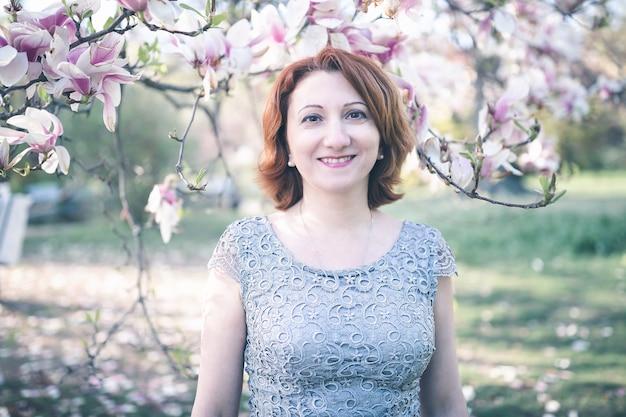 咲くマグノリアの木の下でエレガントなドレスを着た幸せな中年アルメニアの女性。笑って、カメラを見て。トーンのセレクティブフォーカス。
