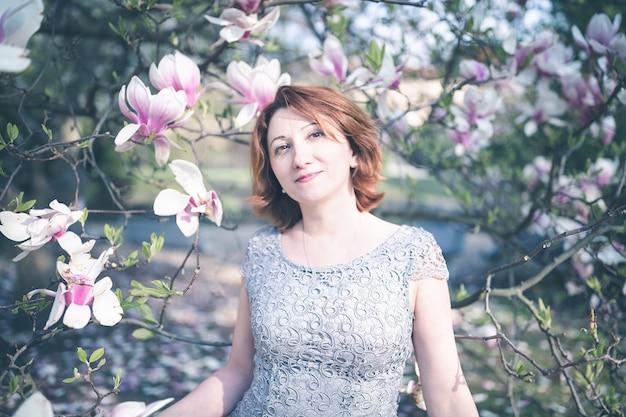 咲くマグノリアの木の下でエレガントなドレスを着た幸せな中年アルメニアの女性。笑顔