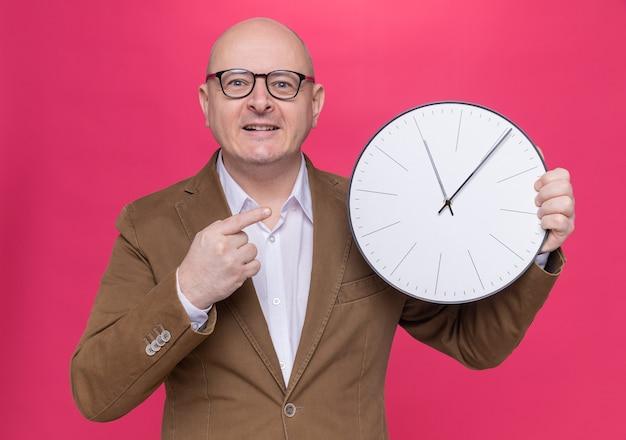 Uomo calvo di mezza età felice in vestito con gli occhiali che tiene l'orologio di parete che indica con il dito indice che sorride allegramente in piedi sopra il muro rosa