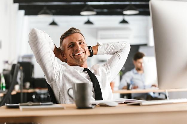 Счастливый деловой человек средних лет расслабляется и смотрит в сторону, сидя за столом в офисе