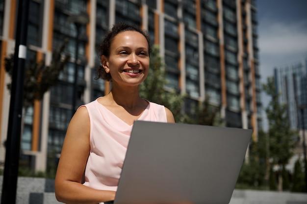 混血民族の幸せな中年ビジネスウーマン、サラリーマン、離れて笑顔、ラップトップを使用して、高い都市の建物の背景の階段に座っている従業員