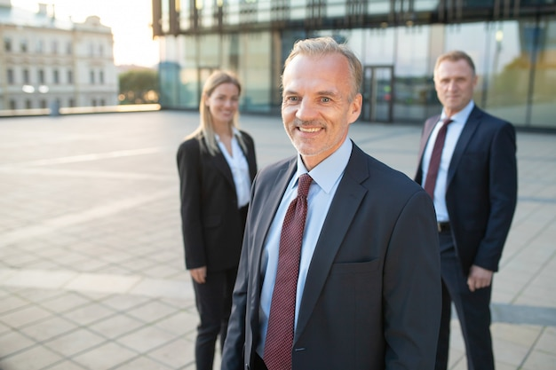 사무실 양복을 입고, 야외에서 서서 카메라를 찾고 행복 중간 나이 든된 사업가. 뒤에 서있는 그의 팀. 팀워크와 팀 성공 개념