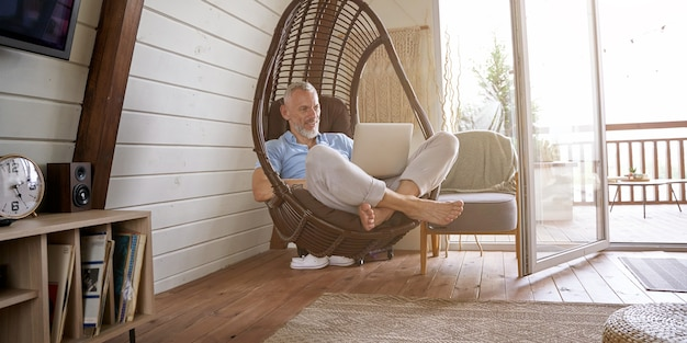 Счастливый кавказский бизнесмен средних лет в повседневной одежде, сидя на кресле-качалке в своем современном