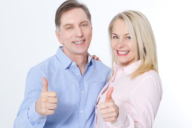 Happy middle aged couple in embraces and show thumb up isolated on white.