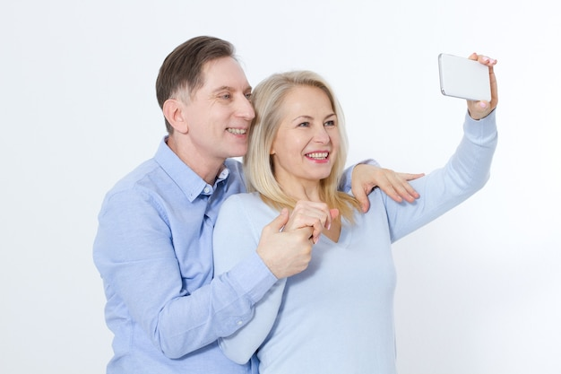 Happy middle aged couple taking selfie with smartphone isolated on white