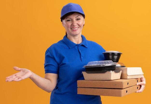 Felice donna di mezza età consegna in uniforme blu e cappuccio che tiene scatole per pizza e confezioni di cibo guardando davanti sorridendo allegramente in piedi sopra la parete arancione