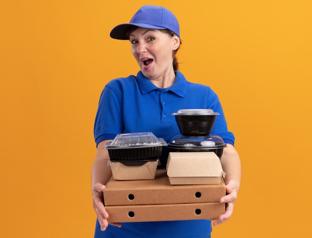 Felice donna di mezza età consegna in uniforme blu e cappuccio che tiene scatole per pizza e confezioni di cibo guardando davanti sorridente allegramente in piedi sopra la parete arancione