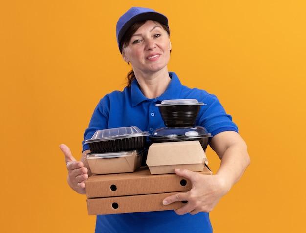 Felice donna di mezza età consegna in uniforme blu e cappuccio tenendo scatole per pizza e confezioni di cibo guardando davanti sorridente fiducioso in piedi sopra la parete arancione