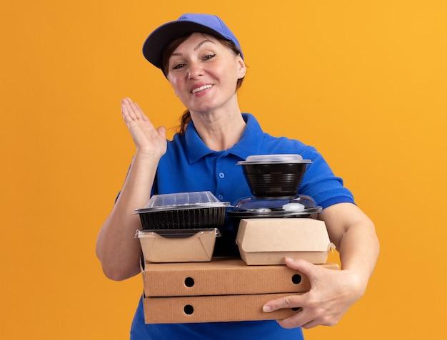 Felice donna di mezza età consegna in uniforme blu e cappuccio che tiene scatole per pizza e confezioni di cibo guardando davanti con il sorriso sul viso in piedi sopra la parete arancione