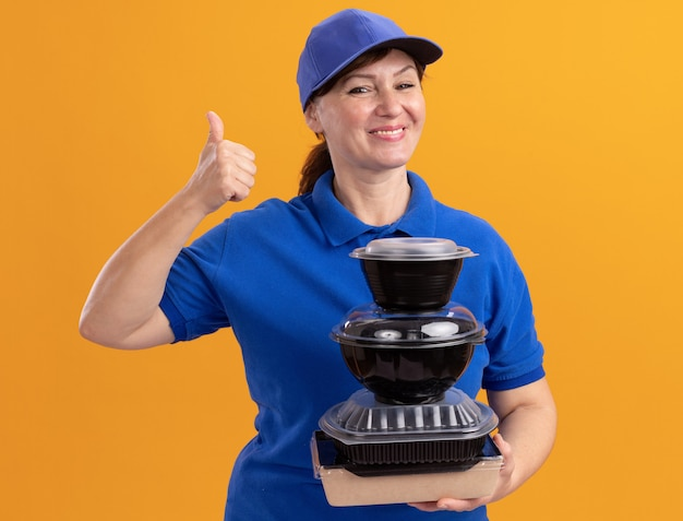 Felice donna di mezza età consegna in uniforme blu e cappuccio che tiene pila di confezioni di cibo guardando davanti sorridendo allegramente mostrando pollice in alto in piedi sopra la parete arancione