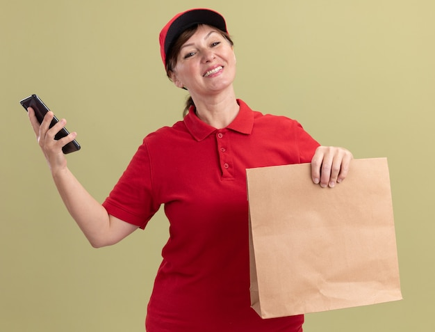 緑の壁の上に立って自信を持って笑顔の正面を見て赤い制服とキャップ保持紙パッケージとスマートフォンで幸せな中年配達の女性
