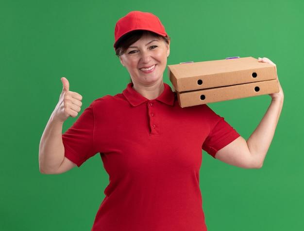 빨간 유니폼과 모자 녹색 벽 위에 서 엄지 손가락을 보여주는 행복 한 얼굴로 웃 고 앞에서 피자 상자를 들고 행복 중간 세 배달 여자